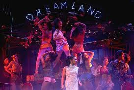 """In April 1975 at """"Dreamland,"""" a sleazy Vietnamese club, shortly before the Fall of Saigon, it is Kim's first day as a bargirl. The seventeen-year-old orphan is greeted by the Engineer, a French-Vietnamese man who owns the club. Backstage, the girls ready themselves for the night's show, jeering at Kim's naïveté (""""Overture""""). The U.S. Marines, aware that they will be leaving Vietnam soon, party with the Vietnamese prostitutes at the club (""""The Heat Is on in Saigon"""")."""